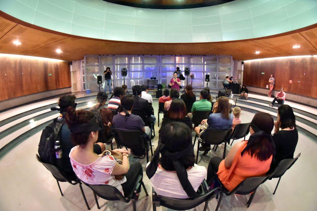 Fotografía de la experiencia donde se ve a un grupo de unas 20 personas sentadas frente a la relatora, rodeados de 5 parlantes en una sala del metro Quinta Normal durante el Día de la astronomía 2018