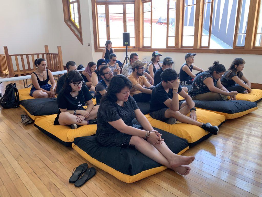 Foto de un grupo de 20 personas sentadas sobre cojines en el suelo, con los ojos cerrados escuchando los sonidos del Viaje Sonoro desde el interior del Sol en el Museo del Sonido en Santiago, Enero 2020.